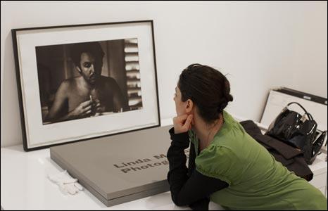 A gallery employee inspects a photograph of Sir Paul McCartney