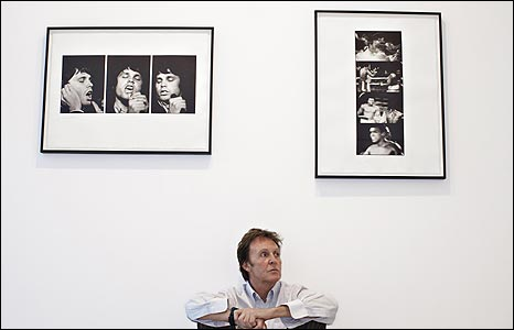 Sir Paul McCartney sitting below pictures of Jim Morrison and Muhammad Ali