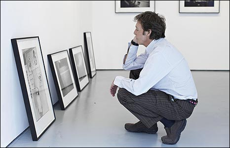 Sir Paul McCartney inspecting a photo taken by his late wife Linda