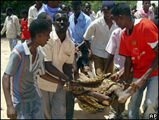 Men carry the body of a man killed during clashes in Mogadishu, Somalia, 21 April, 2008