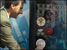 The mayor of Graz applies a mobile use ban sticker to a bus