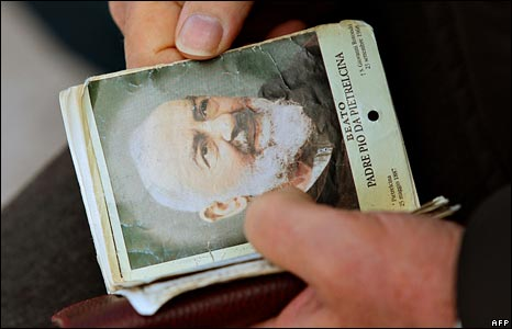 A pilgrim holds a booklet with Padre Pio on the cover in San Giovanni Rotondo in southern Italy