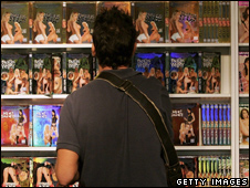 A man browses pornographic DVDs in a shop