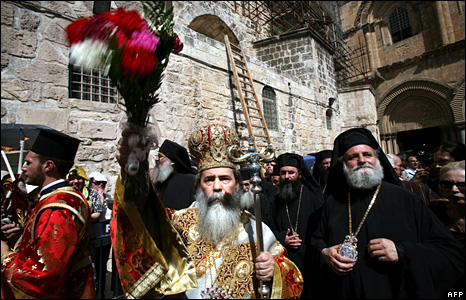 The patriarch of the Greek Orthodox Church in Jerusalem, Theophilos III, sprays holy water at worshippers after the Easter ceremony of the Washing of the Feet