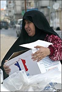 Mujer palestina recibe ayuda humanitaria en Gaza, AFP