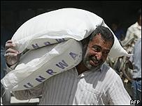 Palestino carga sacos de granos de la ayuda humanitaria de la ONU, AFP