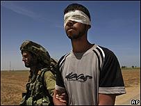 Joven palestino con los ojos vendados, es llevado por un soldado israelí, AP