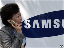Woman walks past Samsung logo in Seoul