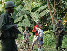 Children stand near government soldiers on a road near Sake 30km west of Goma