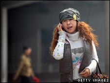 A woman speaks on her mobile phone in Beijing