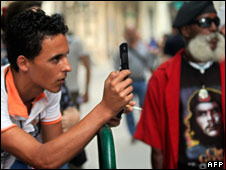 A Cuban takes pictures with his new mobile phone in Havana