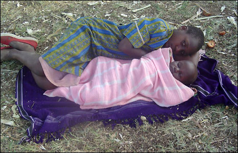 Young mother lies on ground with baby, Nyamira camp. (Picture: Merlin)