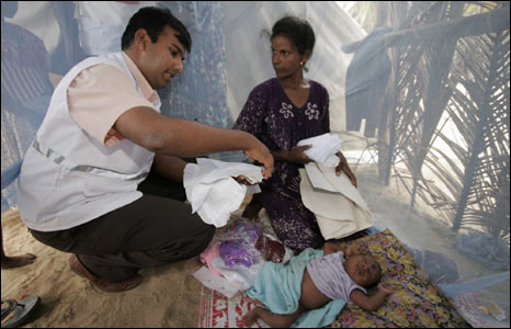 A Merlin doctor with displaced mother and baby in Batticaloa