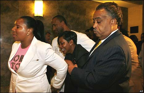 Nicole Paultre Bell, centre, leaves in tears with her mother Laura Paultre, left, and Rev Al Sharpton , right