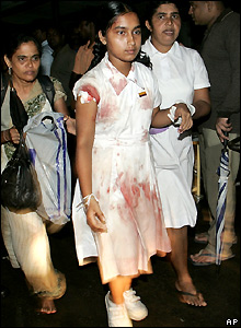 An injured school girl is helped into Kalubowila hospital, Colombo
