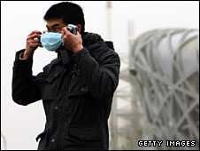 A tourist takes precautions near the Beijing National Stadium