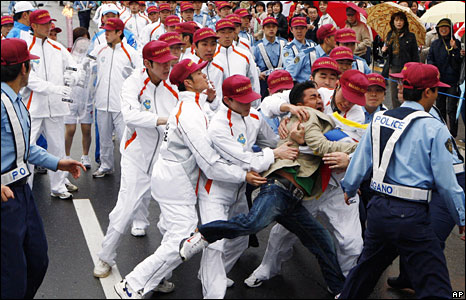 A man is detained by police officers escorting a torchbearer in Nagano, Japan, 26 April, 2008