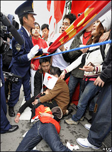A wounded spectator lies on a sidewalk during the Beijing Olympic torch relay in Nagano, Japan, 26 April, 2008