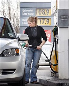 Motorist filling up her car at a petrol station