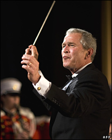 US President George W Bush conducts the US Marine Corps band at the White House Correspondents' Association Dinner on 26 April 2008