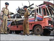 Sri Lankan police guard the wreckage of the bombed bus 26 April 2008