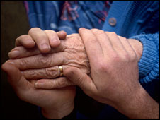 Pensioner's hands being held by a carer