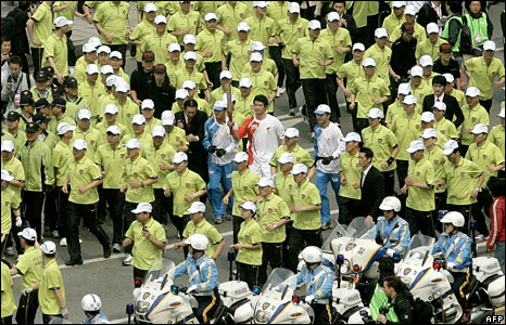A torch runner is escorted by police during the Olympic torch relay in Seoul, 27 April, 2008