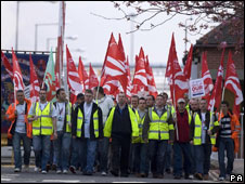 Group of workers holding red and white flags
