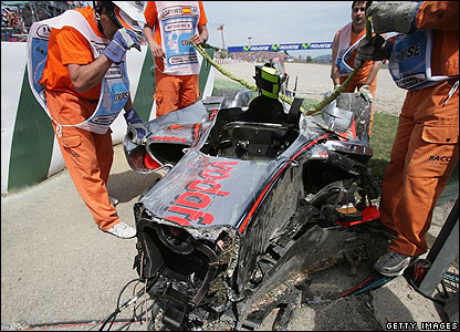 Heikki Kovalainen's damaged McLaren is lifted from the track