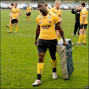 Dwain Chambers carries the pads back after taking part in the pre-match warm-up
