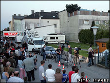 Local people watch police at work at the back of the suspect's house in Amstetten