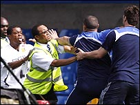 Patrice Evra (left) and a Chelsea groundsman are separated by a steward