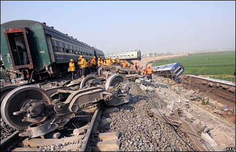 Chinese rescue officials work amongst the wreckage of two trains which collided in Shandong province