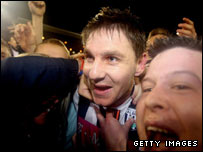 West Brom's Zoltan Gera is mobbed as Baggies fans celebrate their likely return to the Premier League