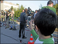 A boy takes a photo of media outside the Fritzl house in Amstetten, Austria, 28 April, 2008