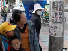 Residents look at pictures of Tibetan protesters wanted by the authorities (27 March 2008)