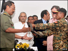 Jose Ramos-Horta (L, back in white shirt) looks on as rebel leader Gastao Salsinha (R) hands in his weapons, 29 April
