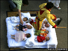 A man dressed as the devil jumps over babies during a religious festival in Spain