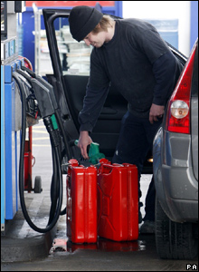 Man filling jerry cans at a filling station