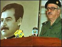 طارق عزيز إلى جانب صورة لصدام حسين