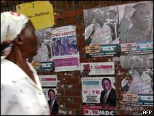 A woman walks past posters of Zimbabwean presidential candidates Robert Mugabe, Simba Makoni and Morgan Tsvangirai in Harare