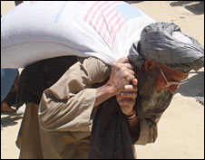 An Afghan man carries a bag of food aid from the US