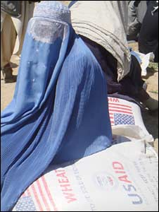 An Afghan woman sits on a bag with food aid