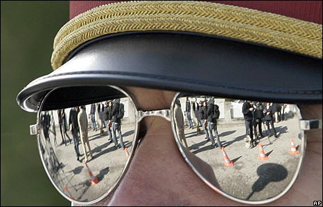People reflected in sunglasses of Austrian policeman
