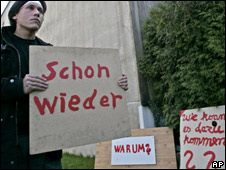 A protester stands outside the Amstetten house with signs expressing disbelief