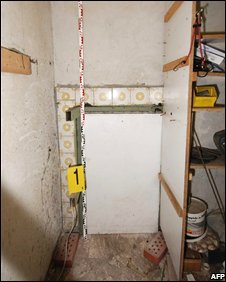 Access door to the cellar with police label and measuring stick