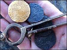 An archeologist holds a Spanish gold coin and three Portuguese silver coins and brass dividers found in the wreck in Namibia