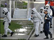 Police wearing protective suits enter an apartment in Konan, southern Japan on 24 April after a similar gas was released by a suicide victim