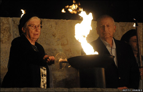 Holocaust survivors light a torch at a ceremony at Yad Vashem