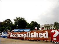 """Manifestantes frente a la Casa Blanca sostienen una manta con la frase de Bush hace cinco años: """"Misión Cumplida""""."""